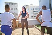 Female yoga instructor teaching class on sunny urban rooftop