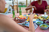 Young woman eating lunch at patio table