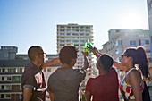 Young friends toasting beer bottles on rooftop balcony