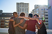 Young friends hugging on sunny urban rooftop balcony