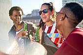 Happy young friends drinking beer on sunny balcony
