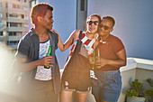 Happy young friends drinking beer on sunny urban balcony