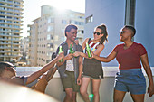 Happy young friends toasting beer bottles on sunny balcony