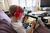 Boy with headphones and tablet playing video game on sofa