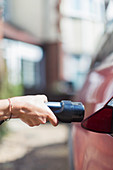 Close up woman recharging electric car