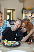 Happy family with dog eating lunch at dining table