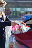 Woman with face mask unloading groceries from car