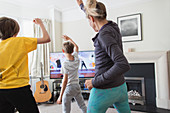 Mother and sons exercising at TV in living room