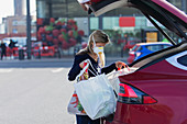 Woman with face mask loading groceries into car