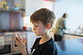Boy using smart phone in kitchen