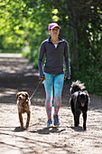 Woman with dogs walking on sunny trail