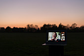 Friends video chatting on laptop screen in park at dusk