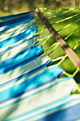 Close up sunshine over blue striped hammock