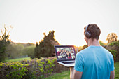Man with headphones video chatting with friends in garden