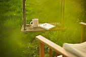Coffee and book on swing in idyllic garden