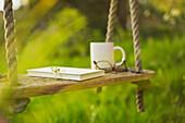 Book coffee and eyeglasses on rustic swing