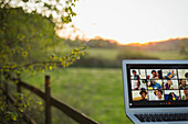 Friends video chatting on laptop screen on rural fence