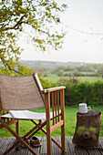 Book and chair on balcony overlooking rural field