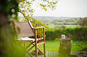 Chair and coffee on tranquil balcony overlooking rural field