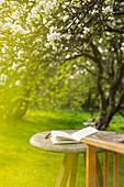 Open journal on table in sunny idyllic garden