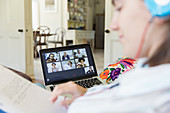 Teenage girl video chatting with colleagues on laptop screen