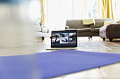 Exercise class streaming on laptop screen behind yoga mat