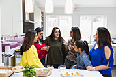 Indian women talking and cooking in kitchen