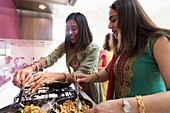 Indian women in saris cooking food at stove in kitchen