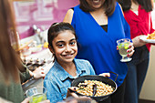 Smiling Indian girl preparing food with family in kitchen