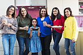 Happy Indian women and girls preparing food in kitchen