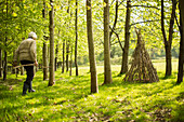 Senior woman with branches making teepee in sunny woodland