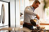 Businessman making tea in morning kitchen