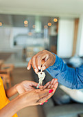Close up man handing house keys to woman