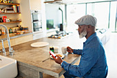 Man enjoying breakfast and using smart phone