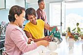 Mature women friends preparing tea in kitchen