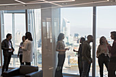 Business people talking at highrise office window