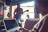 Musicians with laptop and electric guitar