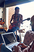 Male musicians with laptop and guitar practicing