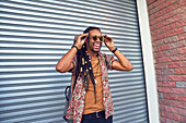 Man with dreadlocks and sunglasses outside garage