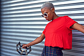 Cool young woman playing tambourine outside garage