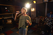 Female musician singing into microphone
