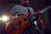 Male musician playing electric guitar on stage