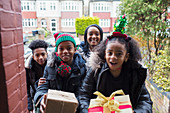 Family delivering Christmas gifts at front stoop