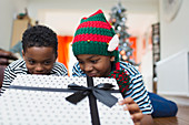 Curious brothers peeking at Christmas gift
