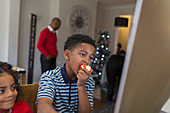 Boy eating apple at home