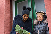 Happy mother and daughter with Christmas wreath