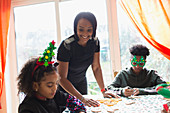 Mother and children decorating Christmas cookies