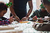 Family decorating Christmas cookies at table