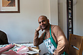 Man in Christmas apron wrapping gifts