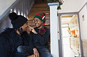 Playful mother and son in Christmas hat on stairs